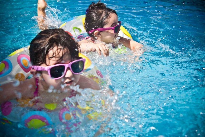 Deux jeunes enfants portant des lunettes de soleil flottant dans une piscine sur des jouets de piscine
