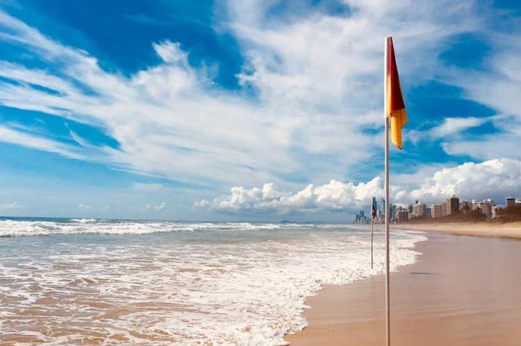 Une plage sans peuple montrant un pôle de sauvetage avec des immeubles de grande hauteur au loin