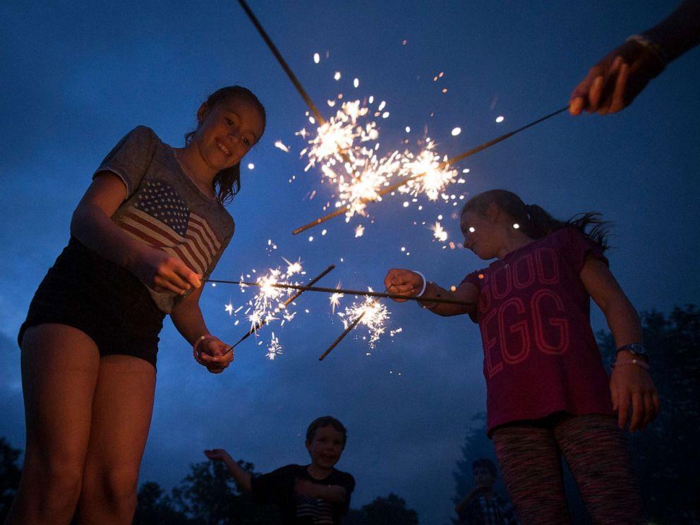PHOTO: Dans cette photo d'archives, Lila Flynn-Tonbragel, à gauche, joue avec des feux de Bengale en attendant le début des feux d'artifice du 4 juillet à Ault Park, le 4 juillet 2016 à Cincinnati.