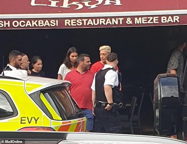 Mesut Oszil (cheveux blonds teints) peut être vu en train de parler aux policiers après l'attaque devant un restaurant turc dans lequel il s'est plongé pour s'échapper