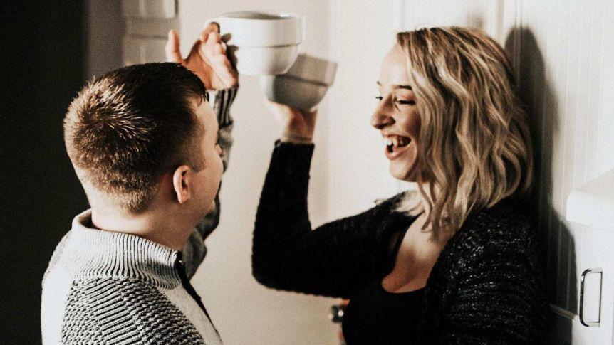 Un homme et une femme dans la cuisine rient ensemble pour une histoire à propos de la soirée, pour une meilleure égalité des tâches ménagères.