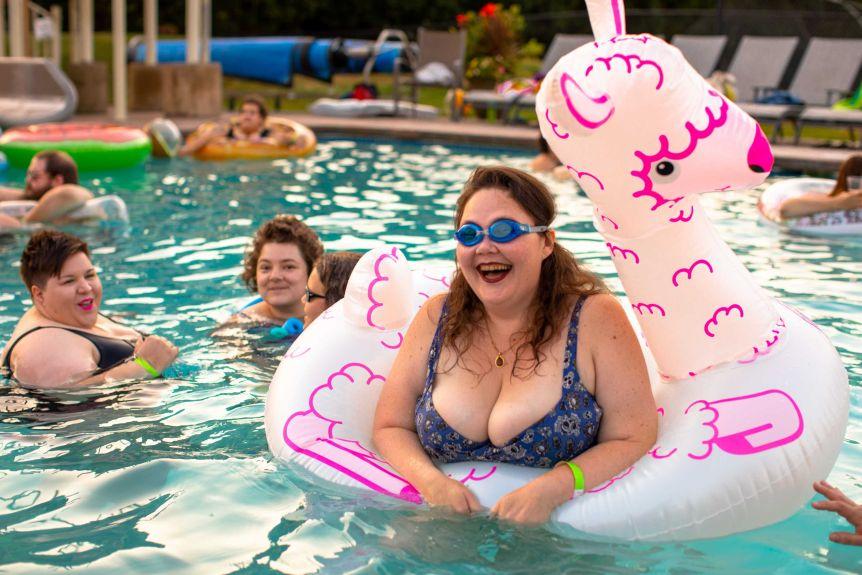 Une femme portant des lunettes de soleil flottant sur un jouet de la piscine et souriant