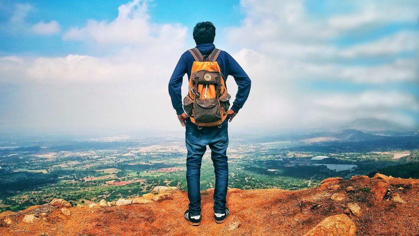 Homme avec sac à dos avec vue panoramique sur les montagnes, la verdure et les bâtiments, histoire de voyager sans famille.
