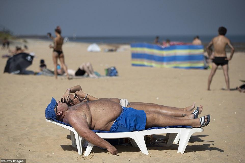 Sur la photo: les baigneurs profitent de la température étouffante d'aujourd'hui en se relaxant sur la plage de Margate, dans le Kent, alors que la Grande-Bretagne fond