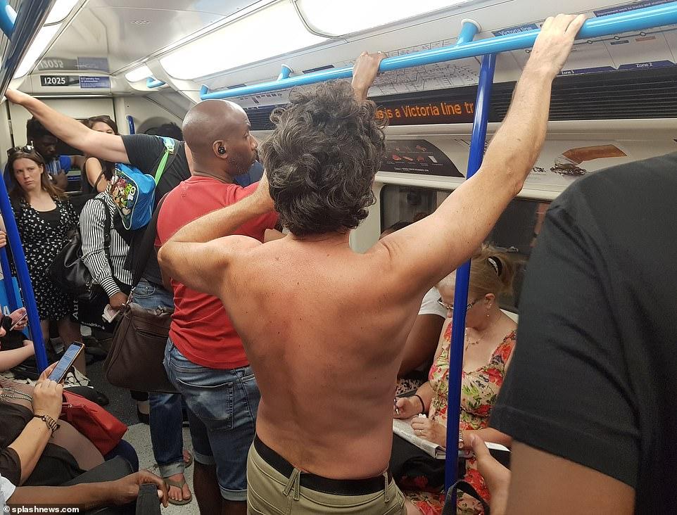 Un passager torse nu sur une ligne de Victoria à l'heure de pointe sur l'étouffant métro de Londres ce matin