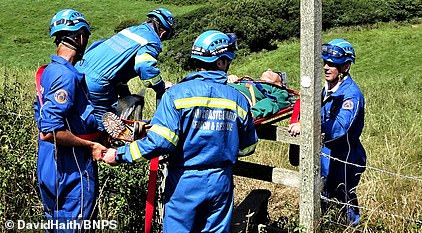 Mr Glynn is carried over a stile en route to an ambulance after coastguards and ambulance paramedics treated him