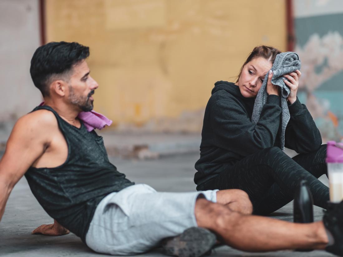un homme et une femme se reposant après une séance d'entraînement.