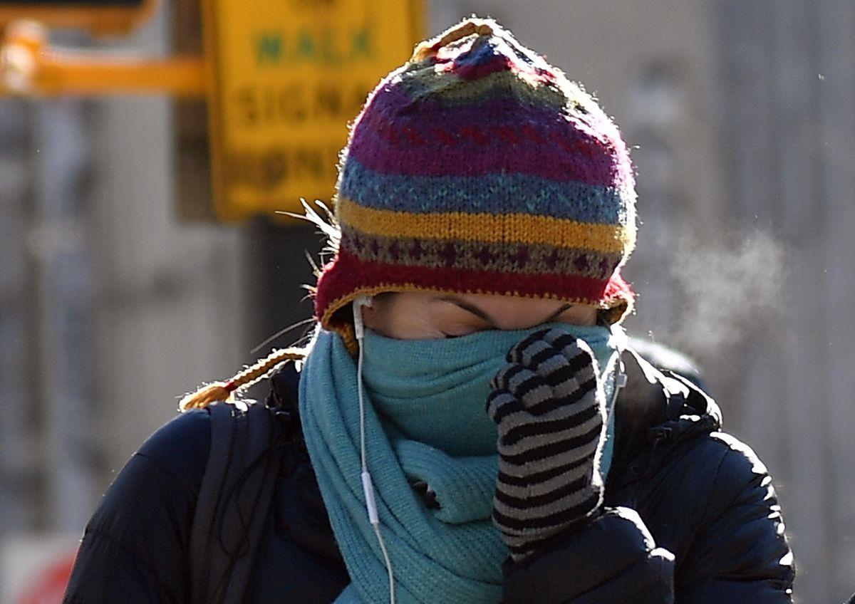 Une femme marchant à Brooklyn le 31 janvier 2019 tient son foulard sur son nez avec sa main gantée.