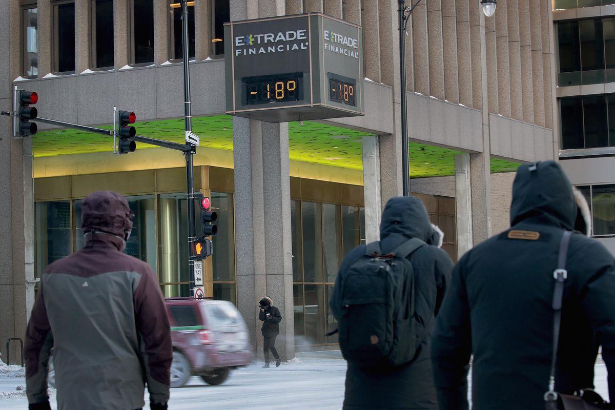Les navetteurs du centre-ville de Chicago le 31 janvier 2019, passez devant une pancarte indiquant «E-Trade Financial: -18 degrés».