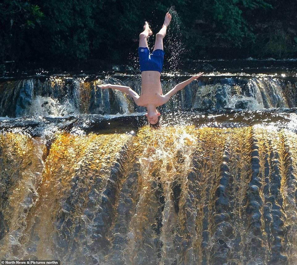 Les nageurs se refroidissent en sautant dans la rivière Swale à Richmond dans le North Yorkshire aujourd'hui alors que la canicule continue