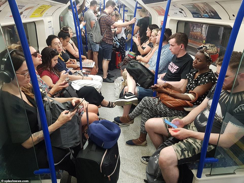 Les navetteurs photographiés à l'heure de pointe sur un train de ligne Piccadilly aujourd'hui sur ce qui a été le jour le plus chaud de juillet