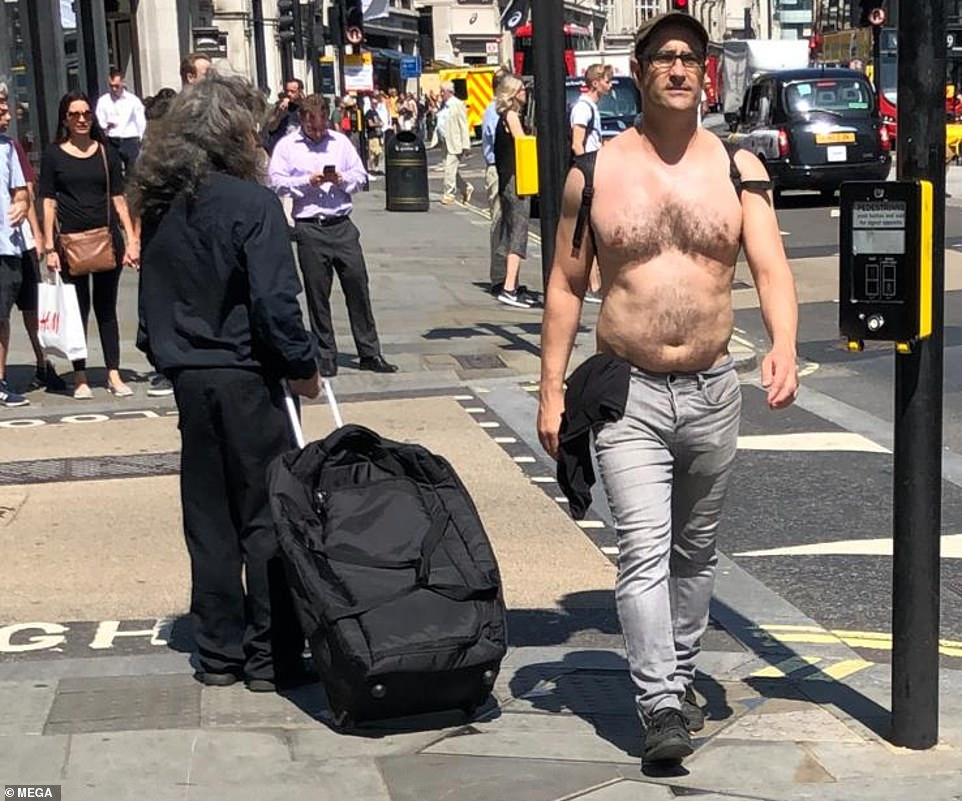 Un homme torse nu marche le long de Regent Street dans le centre de Londres aujourd'hui alors que la capitale endure la canicule