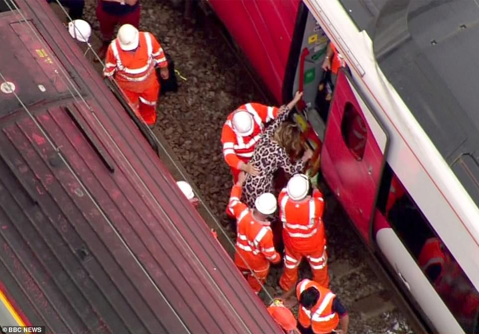 Les travailleurs de la voie libèrent les passagers d'un train dans lequel ils se sont retrouvés coincés et les ont transportés vers un autre alors que les températures en Grande-Bretagne montent en flèche