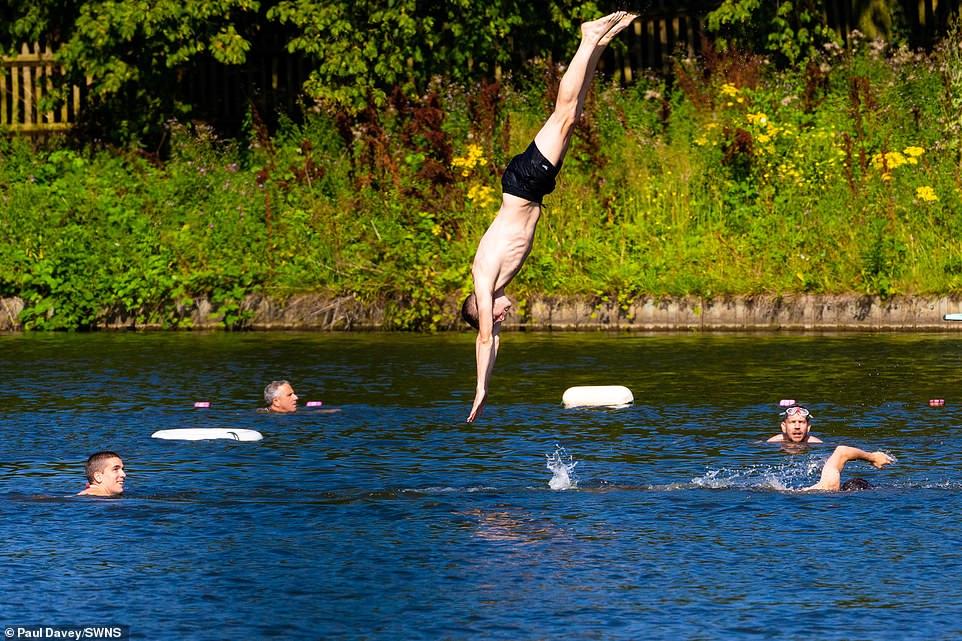 Un homme plonge dans l'eau fraîche à l'étang de baignade pour hommes à Hampstead Heath dans le nord-ouest de Londres aujourd'hui