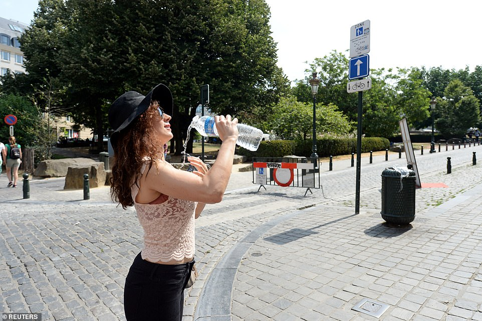 A woman cools off with water on a hot summer day in Brussels, Belgium