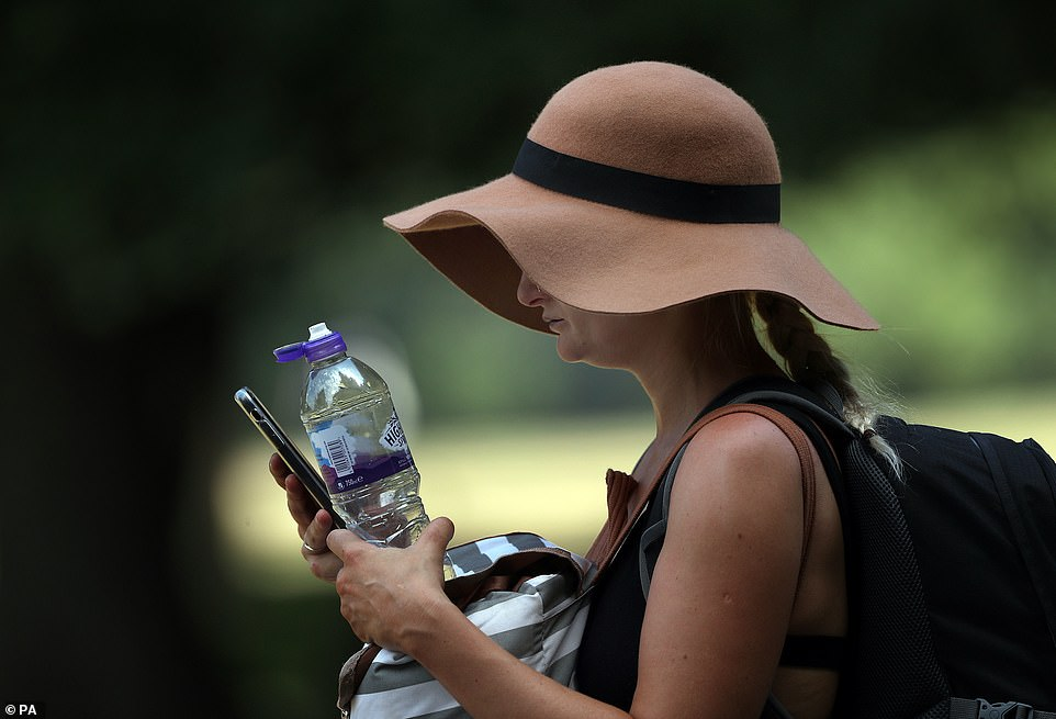 Ayoung woman tries to keep cool in Hyde Park, London, as temperatures soar