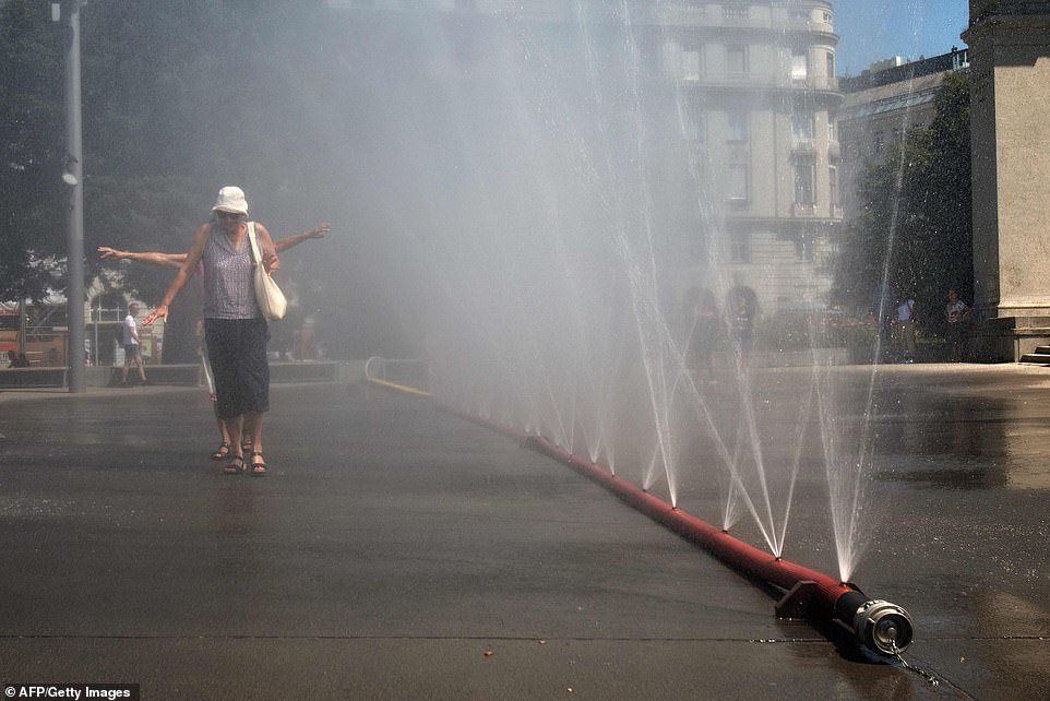 People walk past a curtain of water at the Praterstern Square in Vienna