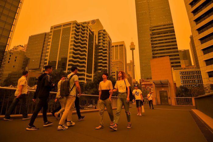 Les gens traversent un pont dans le quartier central des affaires de Sydney, le ciel est orange et brumeux avec la tour de Sydney en arrière-plan.