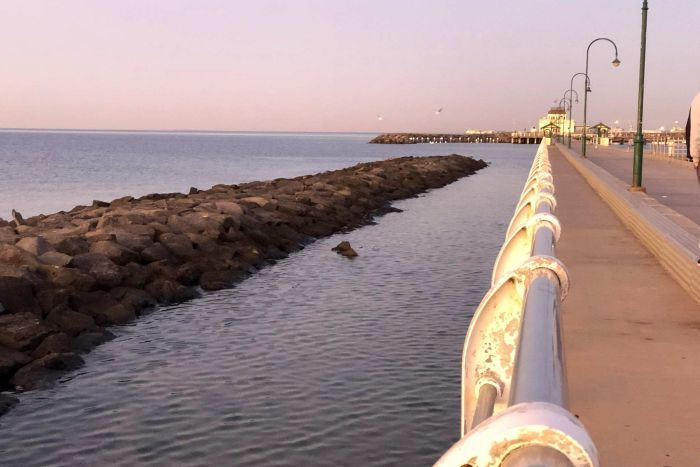 Une lueur rose sur l'horizon donnant sur la baie de Port Phillip depuis la jetée de St Kilda.