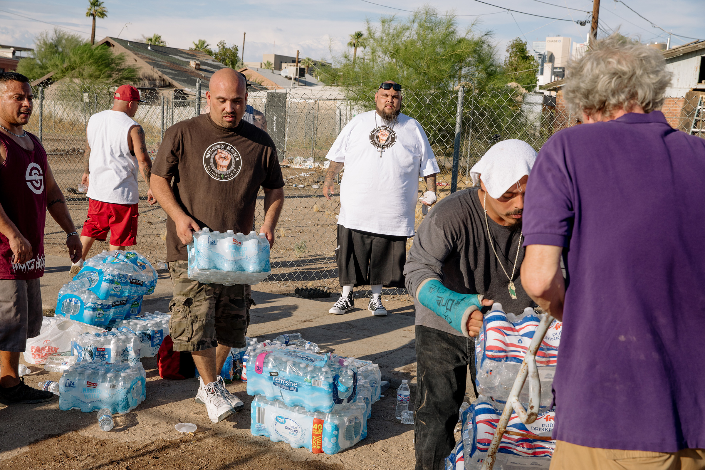 The Brown Boyz music crew distributes water and barbeque to people experiencing homelessness during an excessive heat advisory on July 13, 2019 in Phoenix, Ariz.