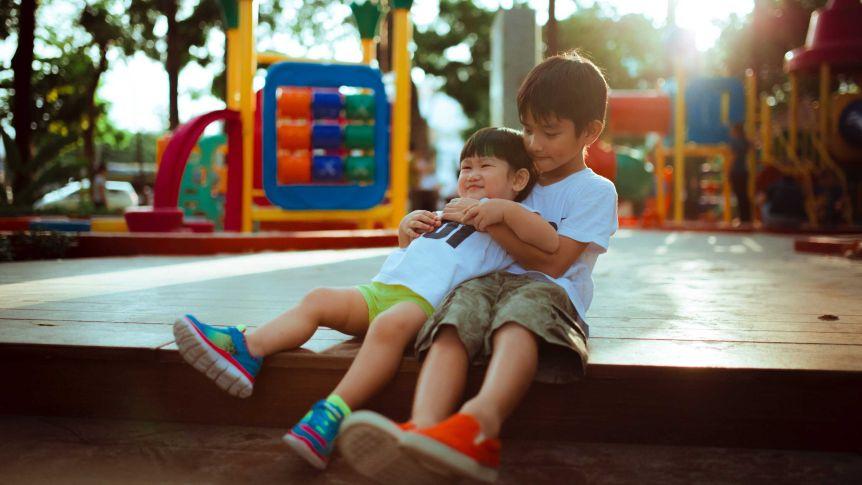 Deux jeunes garçons assis dans une aire de jeux, le plus âgé tient le plus jeune