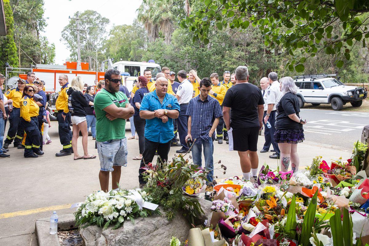 Des civils et des pompiers de Sydney, en Australie, se rassemblent autour d'une collection de bouquets de fleurs à la mémoire de deux pompiers volontaires décédés en combattant des feux de brousse.