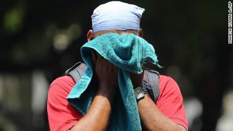 Un Indien utilise une serviette pour essuyer la sueur sur son visage lors d'une journée d'été chaude et humide à Hyderabad, en Inde, le 3 juin 2019.